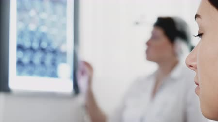 Healthcare and traumatology medicine. Doctor trauma specialist diagnoses injury by x-ray explains to patient her treatment plan. Face tired sick young woman on blur background with doctor, side view.