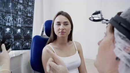 Diagnostic medicine, healthcare at hospital. Doctor diagnosis by x-ray in clinic. She talks with survey patient young woman explains treatment. Physician works at traumatology, diagnostics department. Dostupné videozáznamy