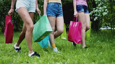 Woman walking in summer city park after shopping together. Girls friends in shorts walk on grass synchronously, legs closeup. Shopping bags in hands. Consumerism concept. Urban leisure young persons.