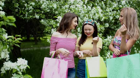Young women looks in paper packages consider purchases together after shopping. Talking, smiling and laughing. Three multi ethnic girls in summer city park. Urban friendship meeting of best friends.