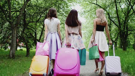 Three young woman friends walk with suitcases in park, back view. Carrying shopping bags, talking and laughing together. Happy tourists travelling. Summer vacation trip travel journey together.