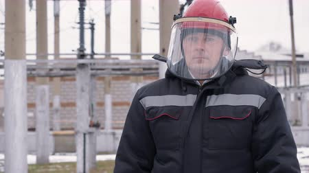 protective suit : Builder man in overalls warm uniform and protective helmet with mask on construction site in northern region. Worker puts mask face works street winter. Harsh working weather conditions in building.