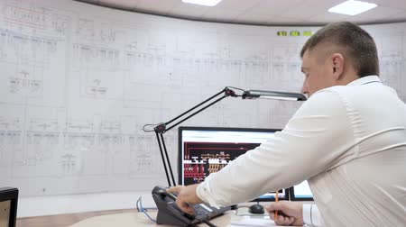 train workers : Dispatcher of railway network in control center room of trains calls on phone. Manager makes paper work. Office room with computer control wall panel with lamp indicators for tracking trains moving.