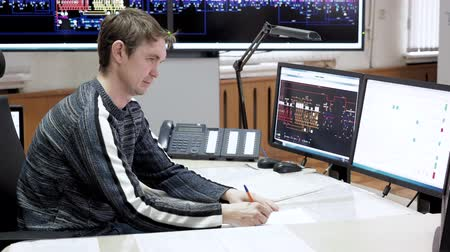 Control room for tracking working equipment on production lines. Man system administrator on production and assembly lines working on computer and calling phone. He talks phone and makes paper work. 動画素材