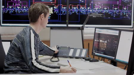 Office with digital screens with schemes tracking electricity objects. Man system administrator working on computer control room of electric power station. He makes paper work and answer phone calls. 動画素材
