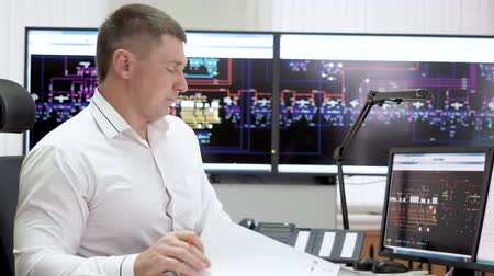Manager calling phone and making paper work. Man office worker operator working in control center room of electric power station using digital screens with schemes. Power and energy industry plant. Dostupné videozáznamy