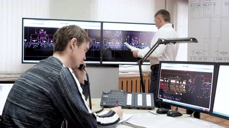 индикатор : System administrator calls phone and talks. Engineer learning documents works with schemes on digital screens. Employees workers of engineering department in electrical power plant working in office. Стоковые видеозаписи