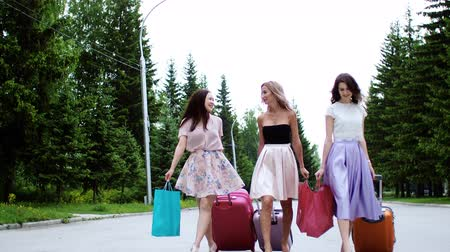 Young women arrive to rest on vacation. Three multi ethnic girls walk street carrying suitcases and shopping paper bags in elegant clothes and heels. Summer vacation trip travel tour journey together.