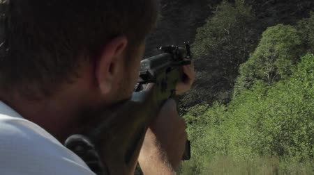 kgb : man shooting a target with ak-47 kalashnikov in mountains