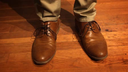 avelã : Man successfully ties his dress shoes