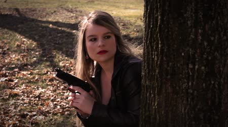 amendment : Female Secret Agent hides behind tree with gun Stock Footage