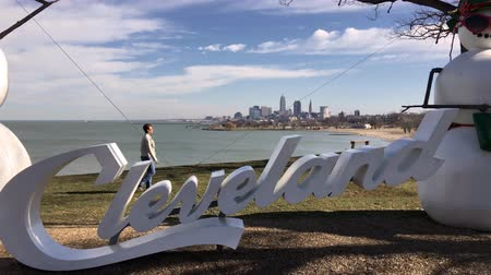Woman walks by Cleveland Sign with skyline in background Stok Video