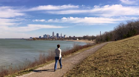 Woman walks down trail with Cleveland skyline in background