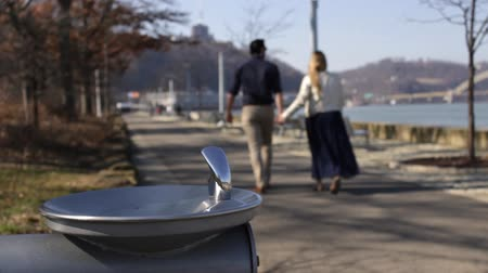Couple walks by water fountain in downtown Pittsburgh