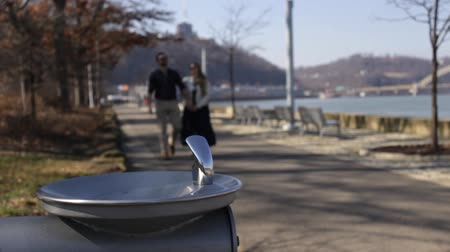 дата : Couple walks by water fountain in downtown Pittsburgh