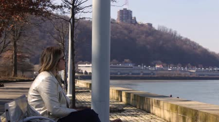 Trendy Woman sits near river in downtown city