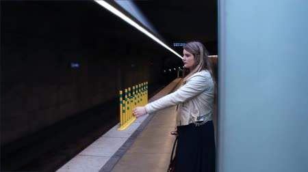 Woman waits for Subway terminal in underground station