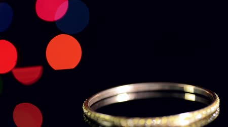ouro : Gold Bracelet on a black background and colorful bokeh