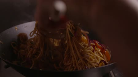 induction cooker : Stirring food in a wok close up shot in slow motion