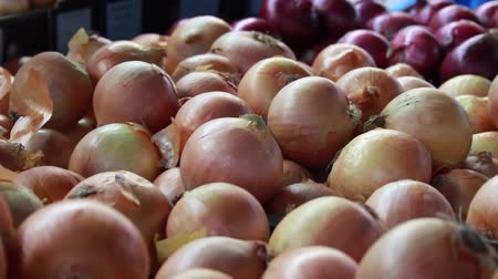 A freehand shot of a pile of onions at a food market