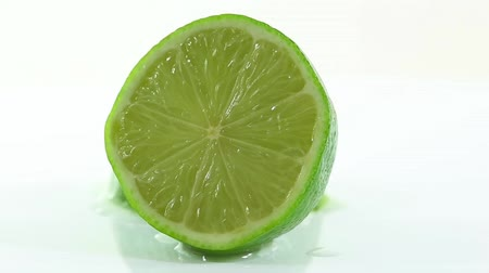 A lime cut in half and arranged on a white background Стоковые видеозаписи