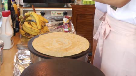 креп : A man bakes crepes on a hot plate and covers them in chocolate sauce
