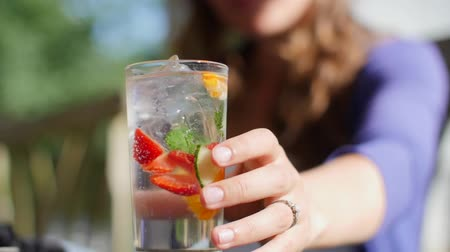 A shot of a lady reaching for a fruity summer cocktail in slow motion Стоковые видеозаписи