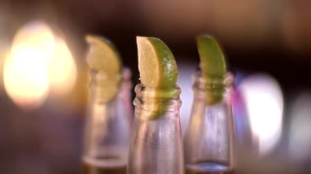 A shot of slices of lime in the top of bottles of beer Стоковые видеозаписи