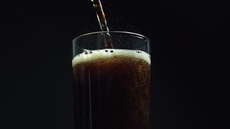 A super slow motion clip of cola being poured into a glass