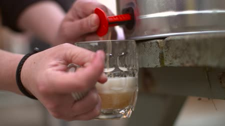 pivovar : A slow motion shot of beer being poured from a keg on a bench