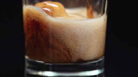 A super slow motion shot of cola being poured into a glass close-up