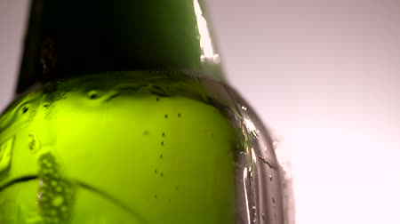 Close up handheld shot of beer bubbles in a green bottle Стоковые видеозаписи