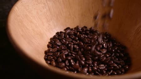 Coffee beans falling into wooden bowl in slow motion