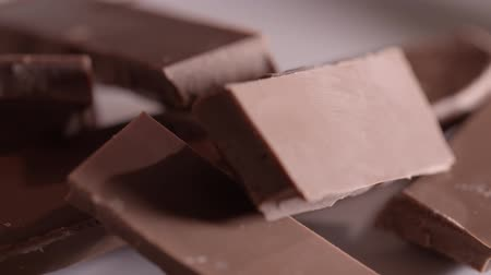 Pieces of chocolate rotating on a plain background Стоковые видеозаписи
