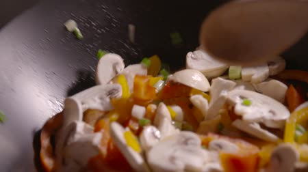 saute : Slow motion clip featuring stir fry vegetables in a pan close up