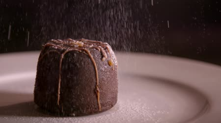 muffin : Slow motion clip of icing sugar being sprinkled on a chocolate dessert