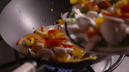 ocet : Slow motion clip of sliced vegetables being poured into a wok ready for frying