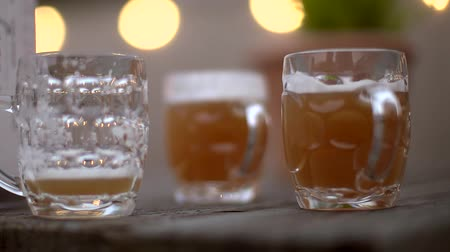 Slow motion handheld shot of 3 beers on a pub garden table