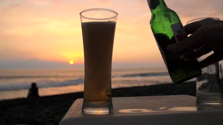 Slow motion shot of beer being poured into a glass on a beach