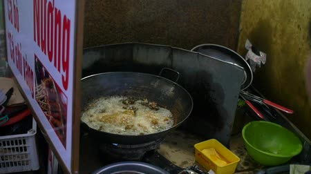 Slow motion handheld shot of a woman cooking street food in Vietnamese town