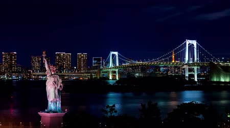 kanto district : night Time lapse of Rainbow bridge in Odaiba, Japan with Statue of Liberty in foreground