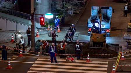 paving blocks : Odaiba, Japan - 9 April 2019 - Roadside construction workers fix sidewalk at night in Odaiba, Japan on the night of April 9, 2019 Stock Footage