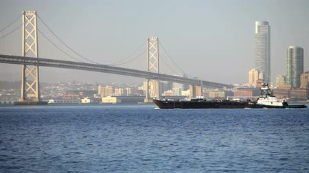 baía : Oakland Bay Bridge with a ship and tugboat crossing the bay