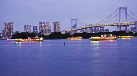 tokio : Lighted boats on Tokyo Bay with Tokyo skyline and Rainbow Bridge, time lapse, Japan