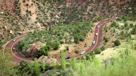 enrolamento : Line of cars driving down an s curve road in Zion National Park