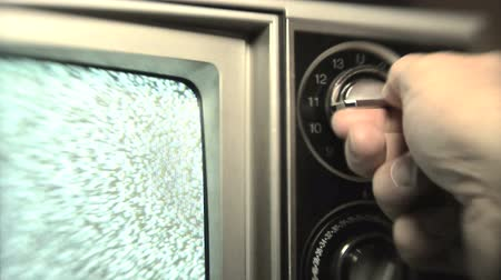 ayarlamak : Man (30s) turning channel knob on retro television stuck on static