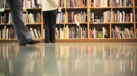 könyvtár : People walking in front of stacks of books
