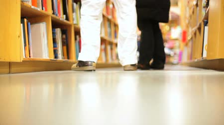 sorok : People walking in front of stacks of books