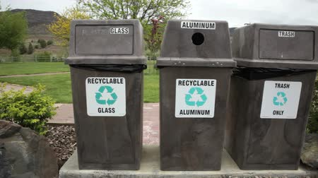 Three recycling bins and trash cans in a park, dolly shot