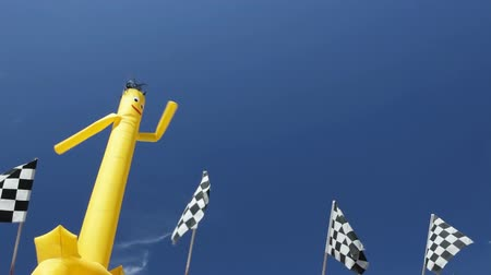 targi : Dancing inflatable figure and checkered flags against blue sky Wideo